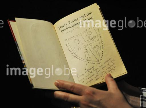 File photo dated 20/5/13 of Dr Philip Errington, Director of Printed Books and Manuscripts at Sotheby's in London holds a first editor Harry Potter book annotated by author JK Rowling, which has sold for £150,000 at auction.